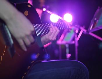 A person sits on a stool and plays their acoustic guitar on a dive bar stage