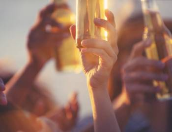 Hands raise beer bottles during a sunset show at a beach bar