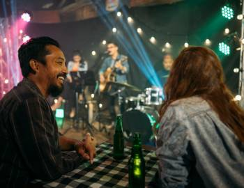 Two people enjoy company over beers in a dive bar while a live band plays on stage